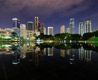 City park with modern buildings in Kuala Lumpur at night reflect Royalty Free Stock Photography