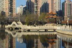 city park. The white bridge the pavilion in the park and the high-rises behind   Tianjin China Royalty Free Stock Photo