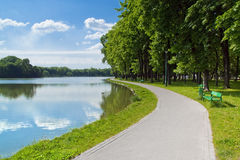 A city park pond shore alley. A random alley at the city park pond shore Royalty Free Stock Photography