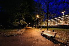 City park at twilight with bench, pathway, alley and trees autumn. Autumn night park. City park at twilight with bench, pathway, alley and trees autumn. Autumn Royalty Free Stock Images