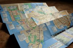 City plan. Partially unfolded New York City map with subway and train routes royalty free stock photo