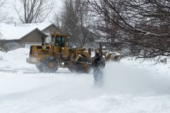 City Plow and Homeowner Plowing. CHANHASSEN, MN - APRIL 14, 2018: City worker and homeowner snowplow during April Minnesota blizzard. The storm deposited 16 Stock Images