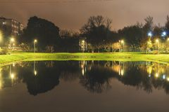 City pond with illumination around the radius with the reflection of lights. Evening time stock image