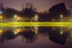 City pond with illumination around the radius with the reflection of lights. Evening time stock photo