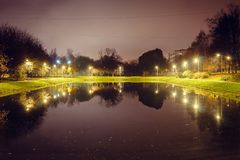 City pond with illumination around the radius with the reflection of lights. Evening time royalty free stock photography