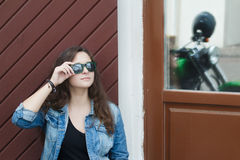City portrait of motorcyclist biker young woman with black mirror sunglasses near green motorcycle boulevard cruiser symmetry refl Royalty Free Stock Images