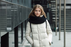 City portrait of young beautiful blonde stylish girl posing in spring fall outdoors in white coat black knitted scarf. Vintage fil Stock Photos