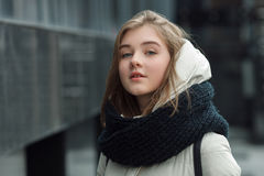 City portrait of young beautiful blonde stylish girl posing in spring fall outdoors in white coat black knitted scarf. Vintage fil Royalty Free Stock Images