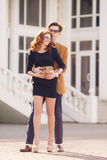 City Portrait of the young couple in love on a sunny day. Outdoor fashion portrait of happy smiling couple in love having fun together end enjoy their love and Royalty Free Stock Image