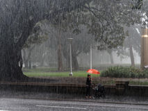 City Rain Storm. A very heavy rain storm, making a blurred vail effect, Hyde Park, Sydney, NSW, Australia, with a red umbrella royalty free stock photo