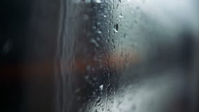 City in rain. A view of a city in rain through the window of a moving tram. Shallow DOF, focus on raindrops on the window