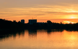 The city reflected in river at sunset. The city reflected in the river at sunset Royalty Free Stock Image