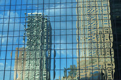 City reflection. Blue sky with buildings reflected in the glass of a commercial building. Bright light and clear Royalty Free Stock Image