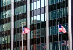 City Reflections. Reflections in an office building with flags also flying and reflected Stock Photo