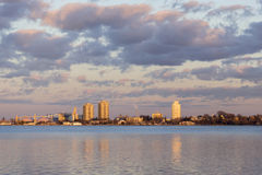 City residential and industrial buidings glowing golden in a vib. Rant sunset across reflecting waters Stock Images