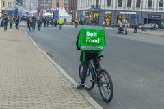 City Riga, Latvia. Fast delivery of food by bicycle. A cyclist stands on the street with a food box. 1