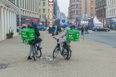 City Riga, Latvia. Fast delivery of food by bicycle. A cyclists stands on the street with a food box. 1