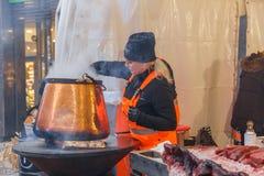 City Riga, Latvia. Street Restaurant food festival. Woman cook meat