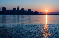 City on the river in sunrise. City, river, sunrise, sunset, sun, building, house, water, sky, blue, light, siberia, krasnoyarsk, Yenisei Royalty Free Stock Photo
