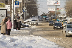 City road cleared from snow. Movement is restored, but difficult. Stock Photos