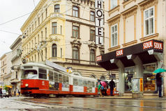 City road after rain and rushing tram between the old houses Royalty Free Stock Photos