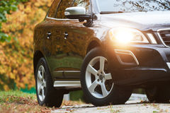 City road safety. SUV automobile car with headlight switched on. At autumn Royalty Free Stock Image