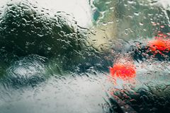 City road seen through rain drops on the car windshield. Focus is on some water drops Royalty Free Stock Image