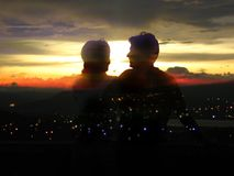 City of Romance. A beautiful effect of a couple watching the sunset over a city at night stock photo