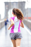 City runner - woman running on Brooklyn Bridge. Rear view backside close up of female athlete training outside in rain in New York City, United States royalty free stock images