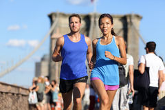 City running couple on Brooklyn bridge. City running couple jogging outside. Runners training outdoors working out in Brooklyn with Manhattan, New York City in stock photo