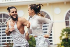 City running couple jogging outside. Runners training outdoors working out in Brooklyn with Manhattan, New York City in. Athletic cheerful couple running stock photos