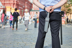 City safety. policeman in the street with metal detector wand. City safety and security. policeman watching order holding metal detector scanner wand in the stock photo