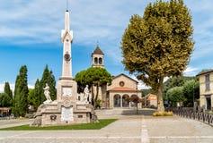 City of San Fermo della Battaglia, province of Como, Italy. Central square with Memorial monument to the fallen and Church in the City of San Fermo della royalty free stock image