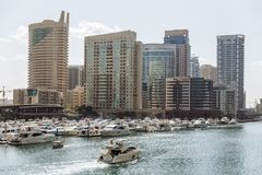 City scape with modern high-rise buildings, man made river with yachts and blue sky in background at Dubai Royalty Free Stock Image