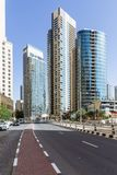 City scape with modern high-rise buildings, road and blue sky in background at Dubai Stock Photo