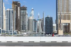 City scape with modern high-rise buildings, street and with man walking in walk way and blue sky in background at Dubai Royalty Free Stock Image