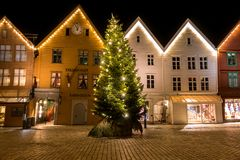 City Scene with A Glittering Christmas Tree in Front of Beautiful Norwegian Traditional Houses in Bergen stock image
