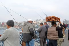 City scene. Peddler bagels between fishermen on the Galata bridge royalty free stock photos