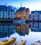 City Scene with Traditional Houses and Boats Reflected in A Calm Canal at Night in Alesund royalty free stock image