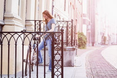City Scene - Woman Parking a Bicycle Royalty Free Stock Image
