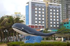 A city sculpture of a whale against the background of modern hotels, Vung Tau, Vietnam. VUNG TAU, VIETNAM - DECEMBER 22, 2015: A city sculpture of a whale Royalty Free Stock Photography