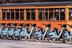 City Sharing Bicycles and Vintage Electric Trolley Car. Blue city sharing of bicycles and an orange metro trolley car depicting environmentally efficient Stock Photo