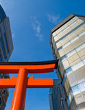 City shrine gate. Shrine torii gate in Kobe city surrounded by tall high rise buildings and blue sky stock image