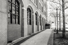 City Sidewalk beside a Brick Building with Arched Windows Royalty Free Stock Images