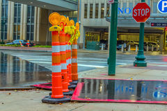 City Sidewalk Hazard Tubes. Orange markers with flashing amber lights at a sidewalk crossing warning pedestrians of street construction and danger royalty free stock photo