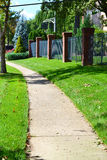 City sidewalk winds through neighborhood Stock Image