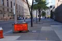 City Sign. A bright orange sign on a city sidewalk Stock Photo