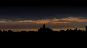 City silhouette against dark sky at dawn Stock Photography