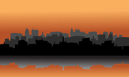 City silhouette reflection of lake. With orange background Stock Images