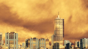 City skyline against cloudy sunset sky. Abstract modern city skyline high rise buildings skyscrapers against scenic sky with golden clouds at sunset or sunrise Stock Image
